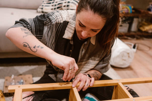 Positive mid adult woman assembling wardrobe furniture at home.