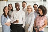 Positive multi racial corporate team posing looking at camera