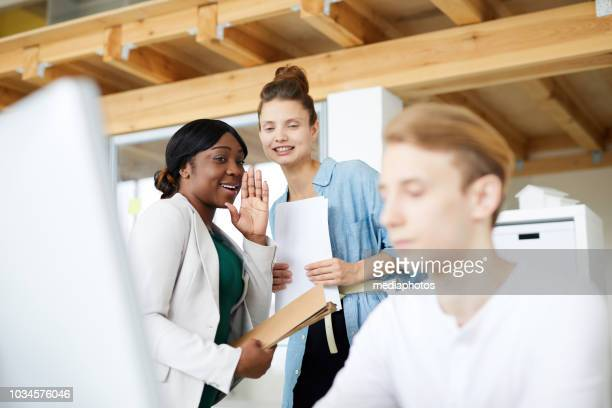 positive multi-ethnic employees gossiping about male colleague using computer in office, black woman sharing information about newcomer with friend - threats stock pictures, royalty-free photos & images