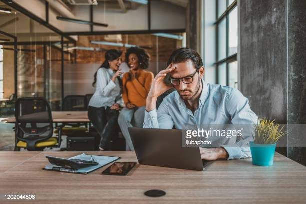 positive multi-ethnic employees gossiping about tired male colleague - bullying stock pictures, royalty-free photos & images