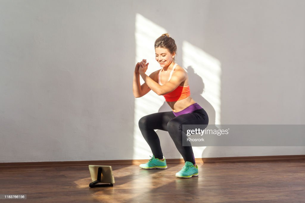Positive sportive woman with bun hairstyle and in tight sportswear doing squatting. indoor studio shot illuminated by sunlight from window : Stock Photo