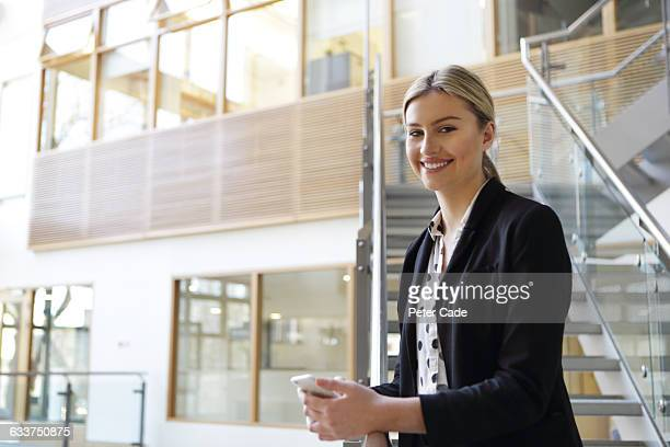 positive woman holding phone wearing suit - digital native stock pictures, royalty-free photos & images