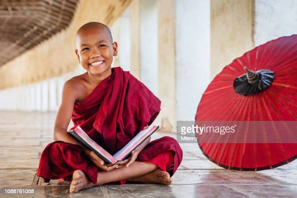 positivity novice monk in monastery archway, myanmar - monk stock pictures, royalty-free photos & images