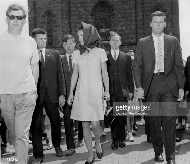 Posse of Irish Special Branch policemen and American Secret Service men escort Jacqueline Kennedy from church after Mass, during a family holiday in...