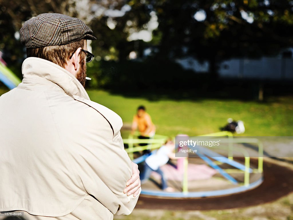 Possible pedophile watches kids play in park : Stock Photo