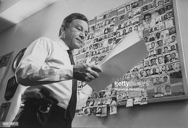 Possibly Police Lt Remo Franceschini looking over a file and standing in front of bulletin board filled w pictures of the Mafia families'...