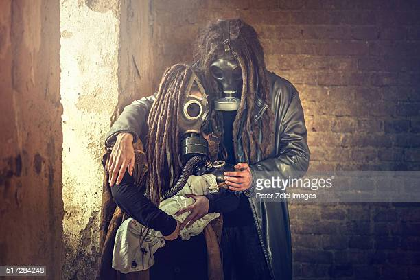 Post apocalyptic survivor family with a baby in gas mask in a ruined building