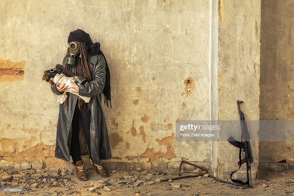 Post apocalyptic survivor holding her baby in gas mask : Stock Photo
