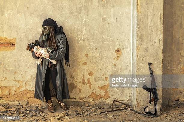 Post apocalyptic survivor holding her baby in gas mask