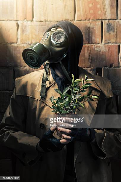 post apocalyptic survivor with a seedling planted in a rusty tin can - cinza nuclear - fotografias e filmes do acervo