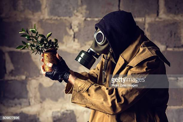 Post apocalyptic survivor with a seedling planted in a rusty tin can
