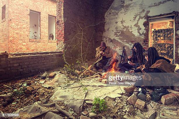 Post apocalyptic survivors camping in a ruined building and eating canned food
