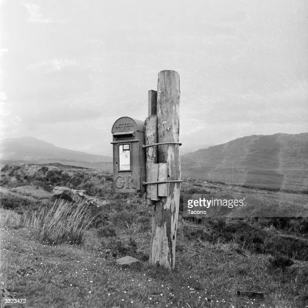 Post box dating from the reign of King George V tethered to a wooden stake in a remote part of the Scottish Highlands.