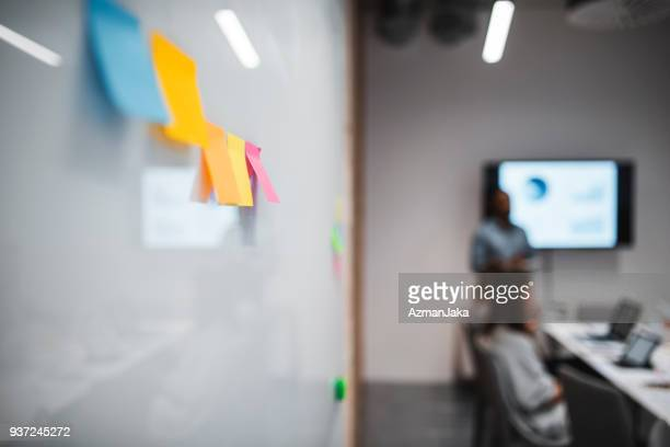 Post it notes in the foreground focus during a business meeting