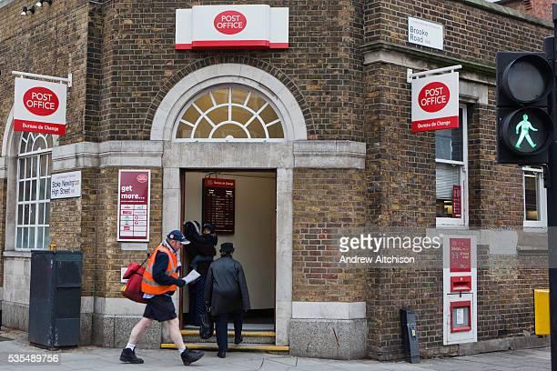 A post man walking past the Post office branch in Stoke Newington Hackney London
