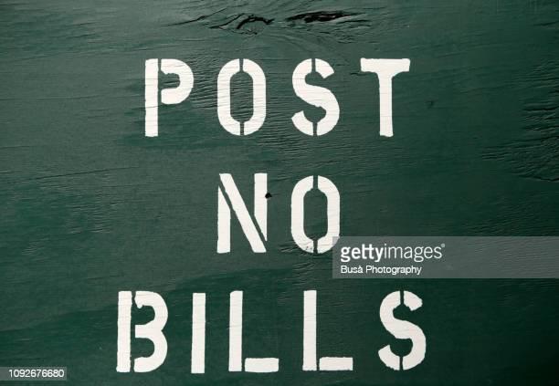 """""""post no bills"""" sign on wooden fence around construction site in the streets of manhattan, new york city - coluna de madeira - fotografias e filmes do acervo"""