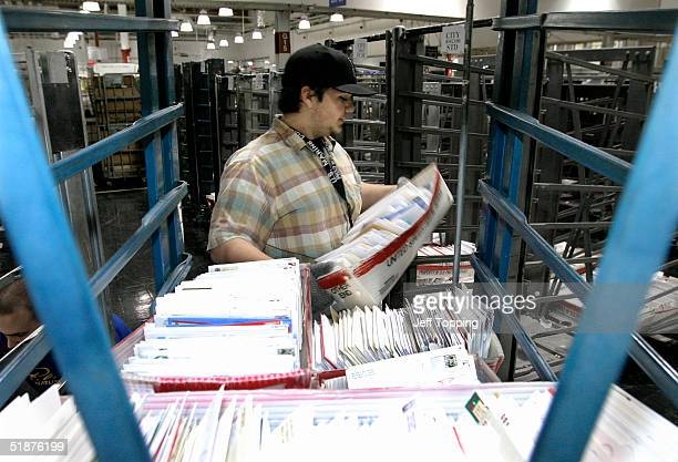 Post Office mail clerk Jesse Preston moves letters from a cart to a sorting area at the Phoenix Processing and Distribution center December 17, 2004...