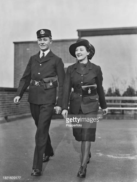 Post Office telegram messenger boy and telegraph delivery girl pose wearing their respective uniforms in London during World War II on 14th February...