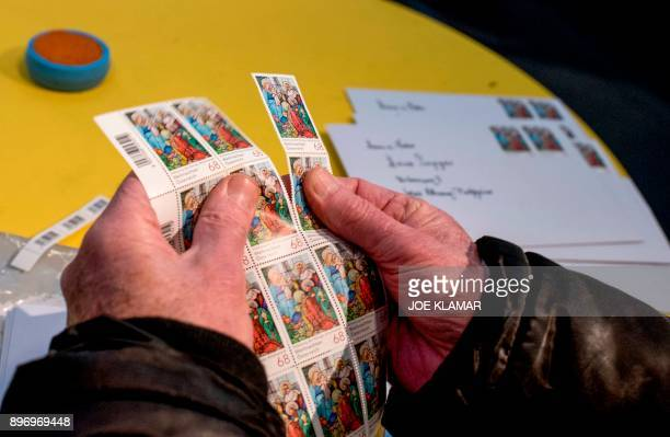 A post office worker stamps envelopes with a special Christmas postmark at the post office in the village of Christkindl Austria on December 14 2017...