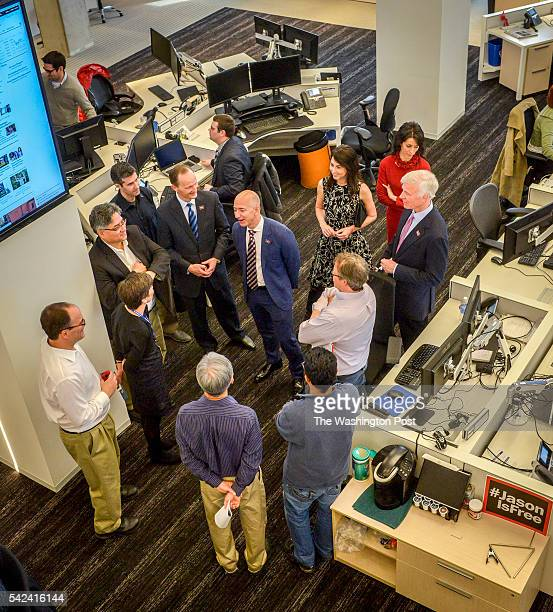 Post owner Jeff Bezos center talks with news executives during a walk through the newsroom after dedication ceremonies for the new Washington Post...