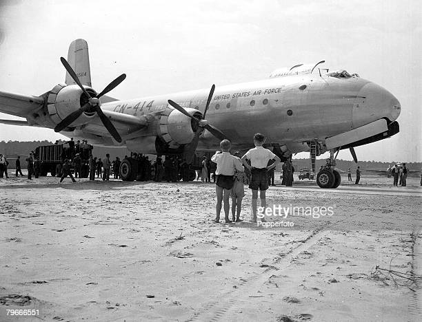 Post World War II, 19th August 1948, Children watch as 20 tons of flour are unloaded from an American C-74 ,Globemaster plane in Berlin to alleviate...