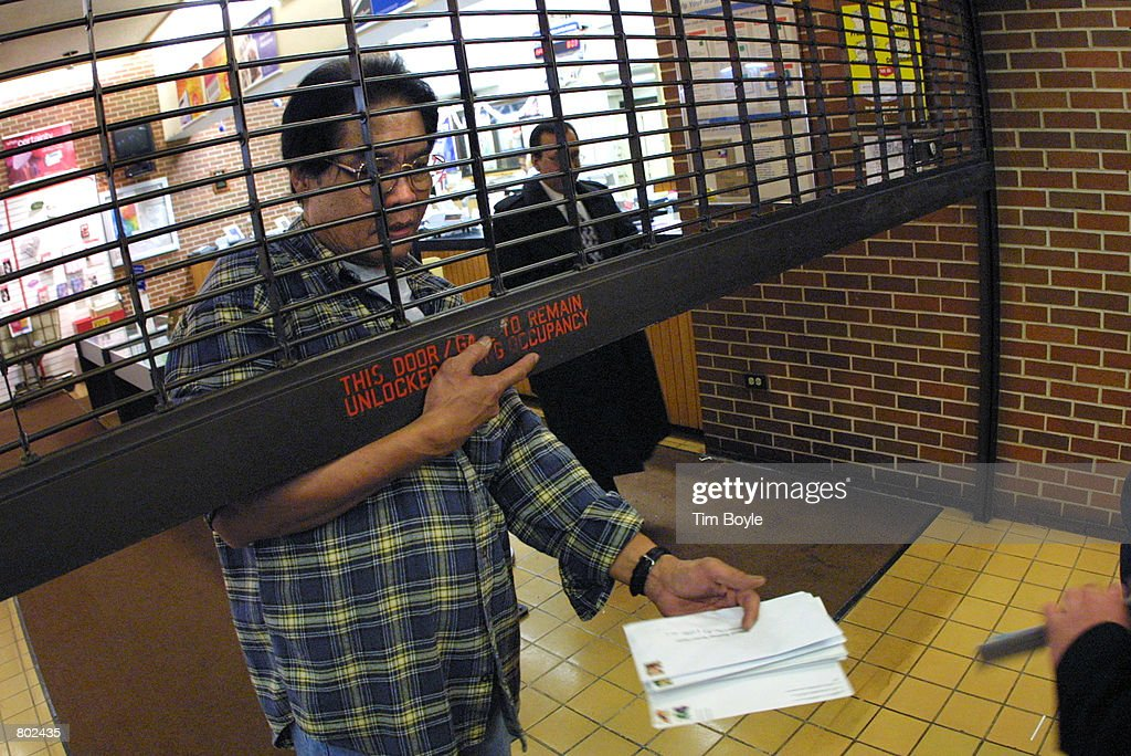 A postal employee accepts tax forms from a last-minute