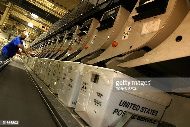 A postal employee attends to an automated sorting machine at the United States Postal Service's processing and distribution center in Capitol Heights...