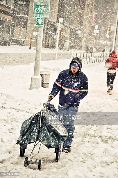 Postal employee delivering mail during winter snowstorm in Manhattan New York City. Winter 2010