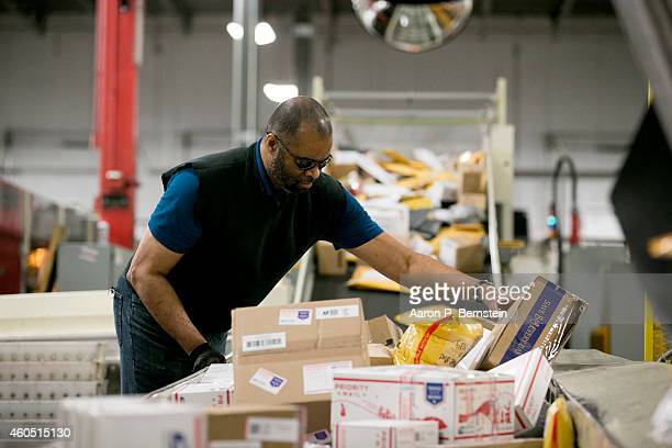 Postal employee Vincent Baxter moves packages at the Indianapolis Mail Processing Annex December 15 2014 in Indianapolis Indiana The US Postal...
