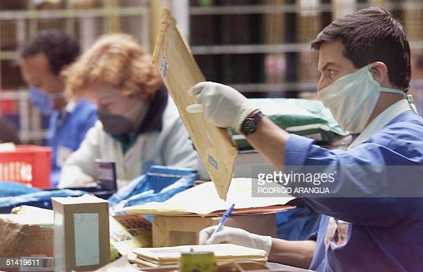 Postal employees in Bogota Colombia sort through the mail using gloves and masks provided by the government after last weeks reports regarding...