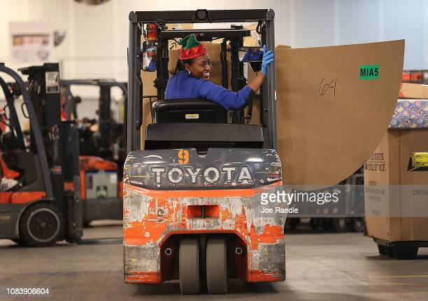 S Postal service mail handler Louvane Virgile drives a forklift carrying packages for sorting at the US Postal service's Royal Palm Processing and...