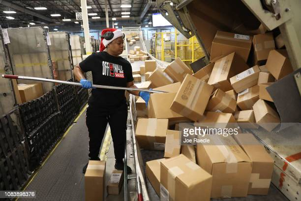 S Postal service mail handler Nikeisha Mitchell sorts packages at the US Postal service's Royal Palm Processing and Distribution Center on December...