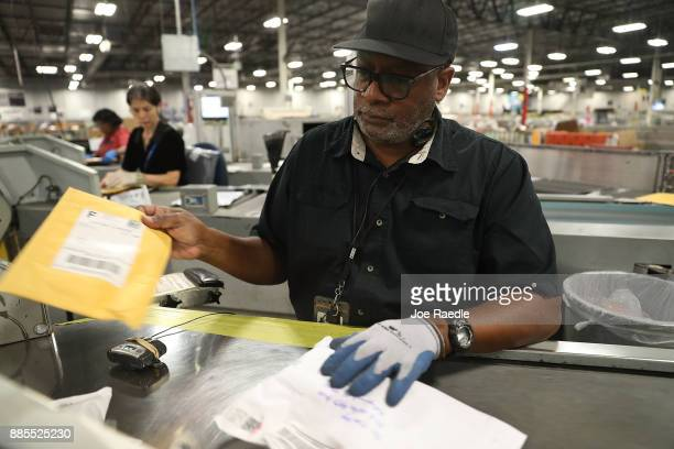 S Postal service mail handler Stephen Johnson sorts packages at the US Postal service's Royal Palm Processing and Distribution Center on December 4...
