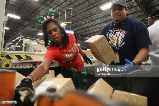 S Postal service mail handlers Barbara Lynn and Daniel Diaz sort boxes at the US Postal service's Royal Palm Processing and Distribution Center on...