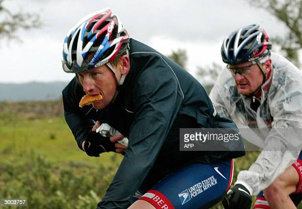Postal team cyclist Lance Armstrong followed by teammate Floyd Landis, eats a cookie during the last stage of the Algarve Tour near Loule 22...
