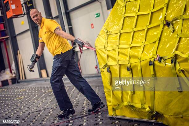postal warehouse worker dragging air cargo container - dragging stock pictures, royalty-free photos & images