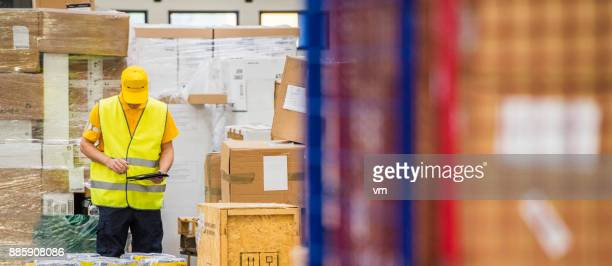 postal warehouse worker examining packages - labeling stock pictures, royalty-free photos & images