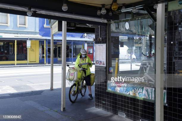 Postal worker delivers mail to a closed bar in Melbourne, Australia, on Tuesday, Sept. 1, 2020. A twin-speed economy is developing in Australia and...
