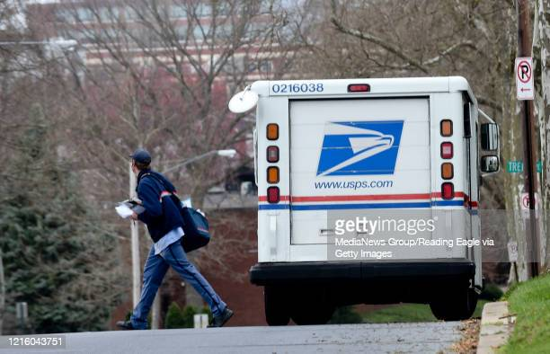 A postal worker delivers mail Tuesday March 31 in the 1100 block of Penn Avenue in Wyomissing amid fears that coronavirus could be spread through the...