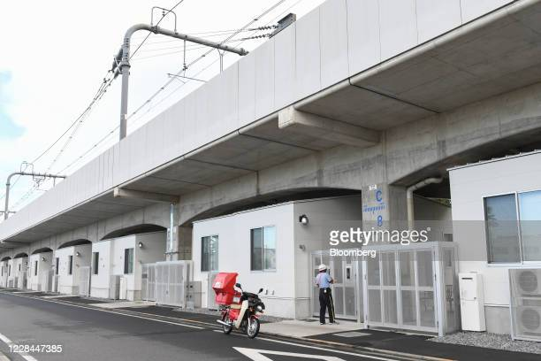Postal worker delivers mails to a dormitory for university students built under railway tracks in Tokyo, Japan, on Thursday, Sept. 3, 2020. In Tokyo,...