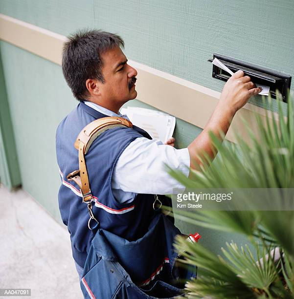 us postal worker dropping letter in mail slot, elevated view - postal worker stock pictures, royalty-free photos & images