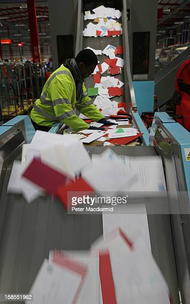 A postal worker feed letters into an automatic sorting machine at Royal Mail's Medway Sorting Centre on December 18 2012 in Rochester England The...