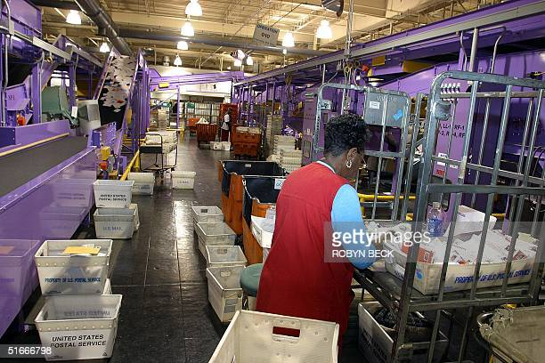 A postal worker handles holiday greeting cards and other mail at the center of a giant purple sorting machine at the United States Postal Service's...