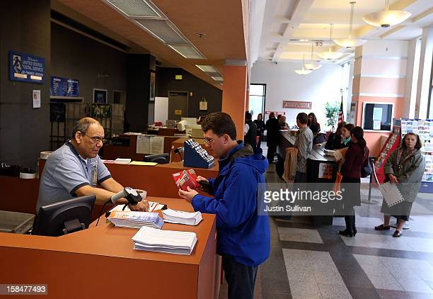 A postal worker helps a customer at the United States Post Office at Rincon Center on December 17 2012 in San Francisco California Customers line up...