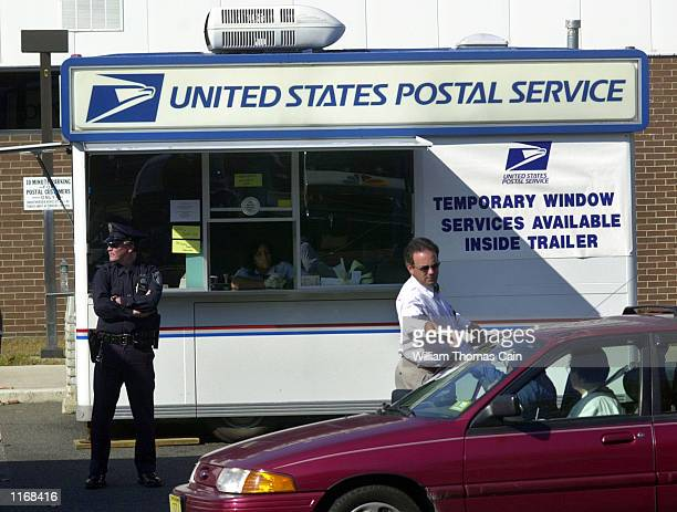 A postal worker is handed mail from a drive up customer outside the Hamilton Mail Processing Center while a policeman stands guard October 24 2001 in...