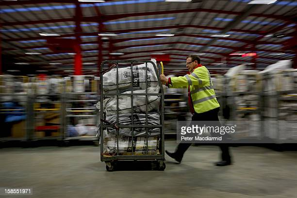A postal worker pushes a trolley full of post to be sorted at Royal Mail's Medway Sorting Centre on December 18 2012 in Rochester England The...