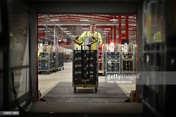 A postal worker pushes sorted post to be placed on a delivery truck at Royal Mail's Medway Sorting Centre on December 18 2012 in Rochester England...