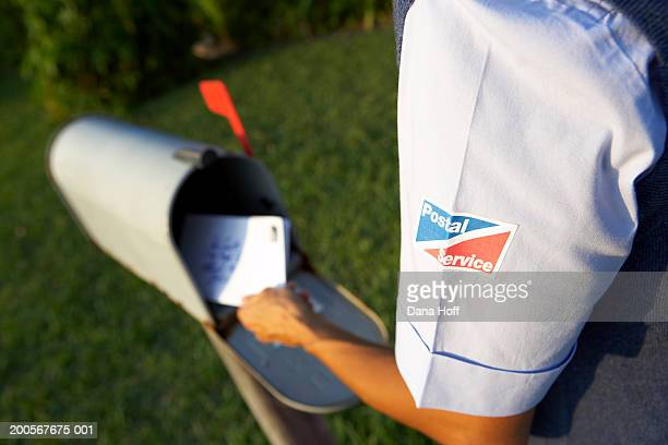 Postal worker putting mail into mailbox, mid section, rear view