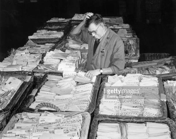 A postal worker scratches his head in confusion as he looks at the hundreds of letters addressed to 'Santa' which arrived at Mount Pleasant post...