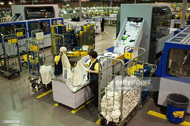 Postal workers empty mail sacks into a letter sorting machine at the central sorting office of Sociedad Estatal Correos y Telegrafos SA also known as...